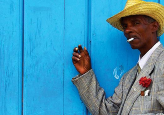 cuban man smoking against a blue background